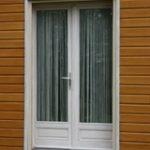 porte-fenêtre entourée d'un bardage en bois traité